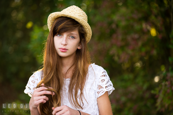 Pretty girl with hat playing with her long hair. Easton, Centreville, Maryland, High School senior portrait session by photographer Leo Dj Photography. http://leodjphoto.com
