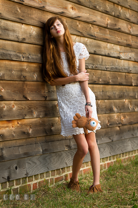 Pretty girl leaning on wooden wall holding stuffed toy from Disney Pixar movie, Monster Inc. Easton, Centreville, Maryland, High School senior portrait session by photographer Leo Dj Photography. http://leodjphoto.com