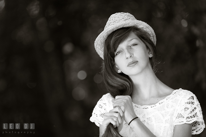 Girl in white dress and hat playing with heir hair. Eastern Shore, Maryland, High School senior portrait session by photographer Leo Dj Photography. http://leodjphoto.com