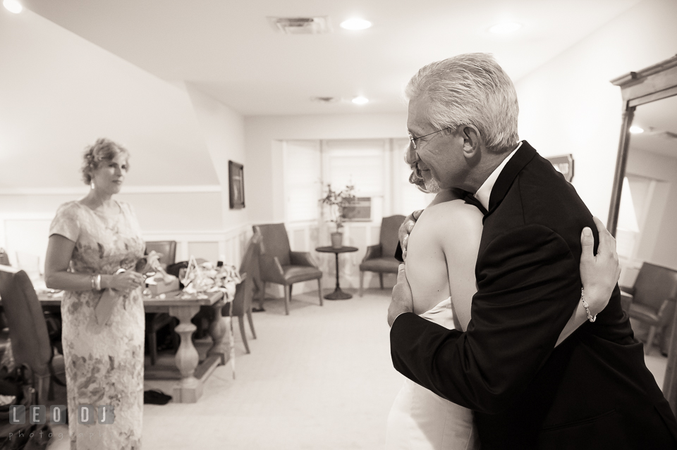 Father of the Bride and daughter hugging during first look, watched by Mother. Kent Island Maryland Chesapeake Bay Beach Club wedding photo, by wedding photographers of Leo Dj Photography. http://leodjphoto.com