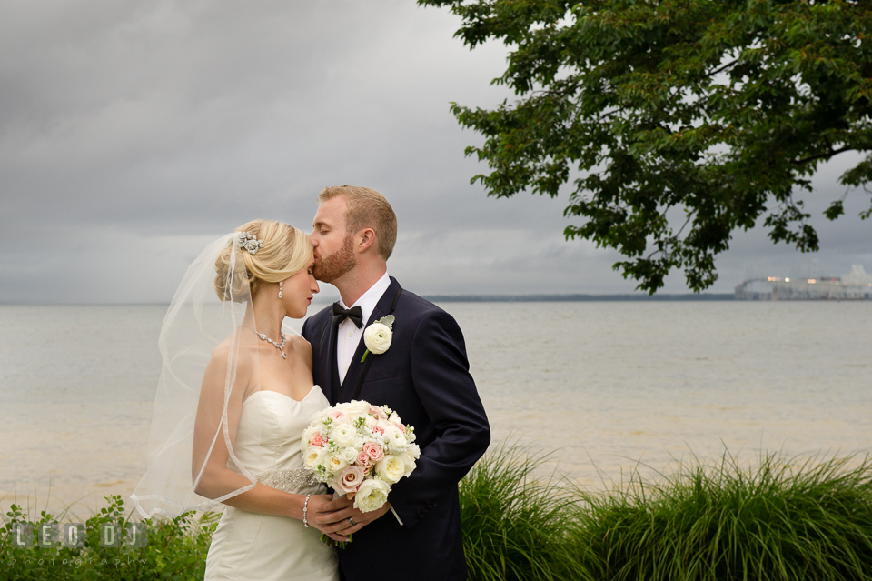 Groom kissed Bride on forehead outside by the water with stormy clouds. Kent Island Maryland Chesapeake Bay Beach Club wedding photo, by wedding photographers of Leo Dj Photography. http://leodjphoto.com