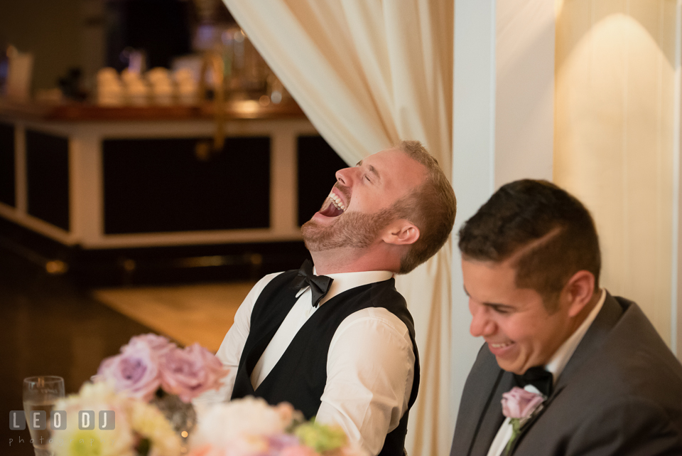Groom laughing hard listening to speech from Best Man. Kent Island Maryland Chesapeake Bay Beach Club wedding photo, by wedding photographers of Leo Dj Photography. http://leodjphoto.com