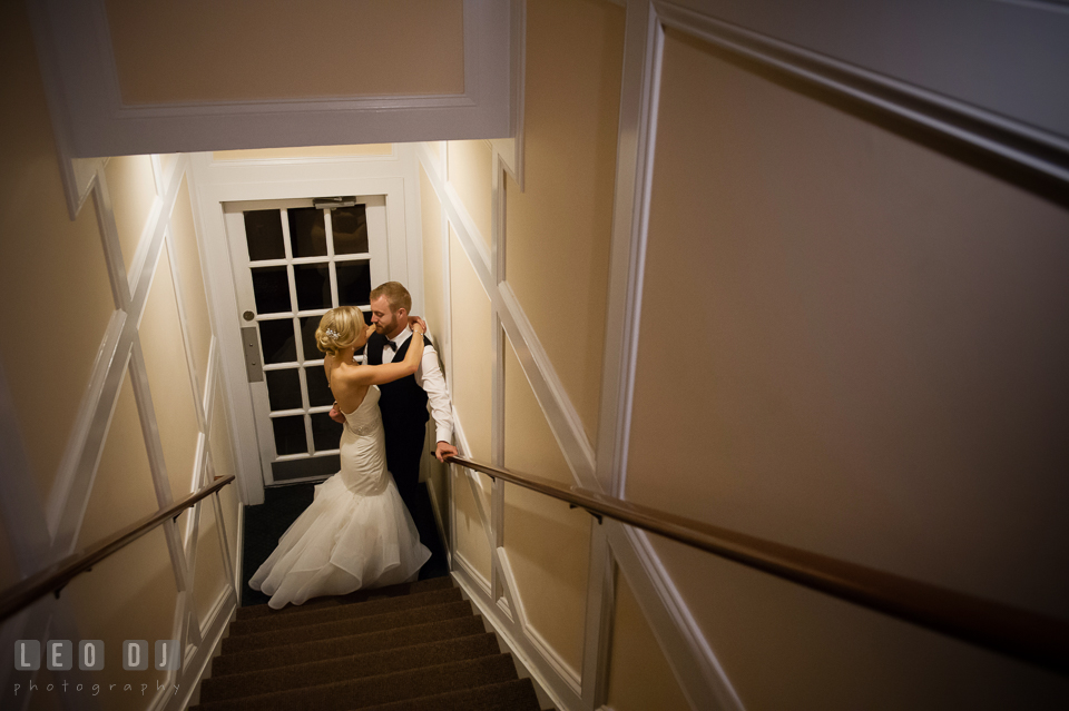 Bride and Groom hugging at the bottom of the stairs. Kent Island Maryland Chesapeake Bay Beach Club wedding photo, by wedding photographers of Leo Dj Photography. http://leodjphoto.com