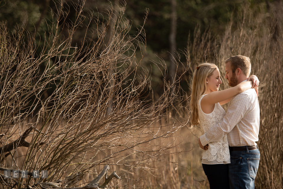 Engaged man and his fiancee embracing each other by the woods. Quiet Waters Park Annapolis Maryland pre-wedding engagement photo session, by wedding photographers of Leo Dj Photography. http://leodjphoto.com