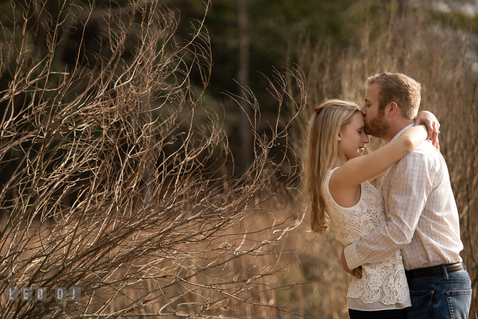 Engaged girl kissed on the forehead by her fiance. Quiet Waters Park Annapolis Maryland pre-wedding engagement photo session, by wedding photographers of Leo Dj Photography. http://leodjphoto.com
