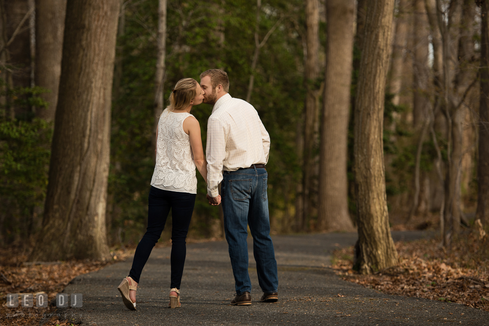 Engaged couple in the woods holding hands and kissing. Quiet Waters Park Annapolis Maryland pre-wedding engagement photo session, by wedding photographers of Leo Dj Photography. http://leodjphoto.com