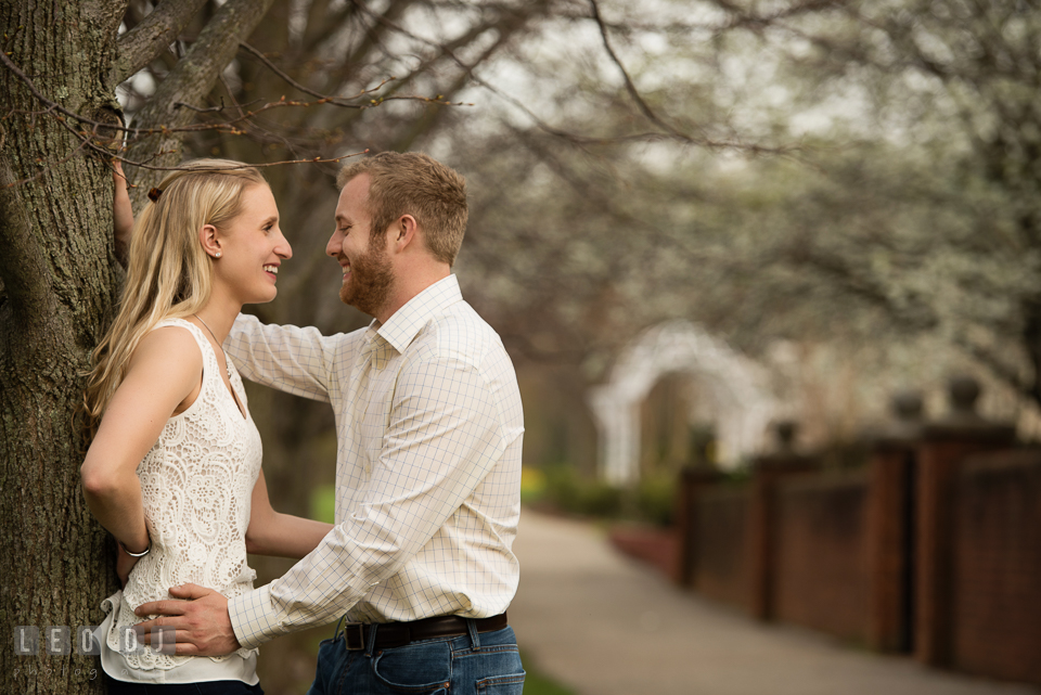 Engaged couple embracing and laughing together by a tree. Quiet Waters Park Annapolis Maryland pre-wedding engagement photo session, by wedding photographers of Leo Dj Photography. http://leodjphoto.com