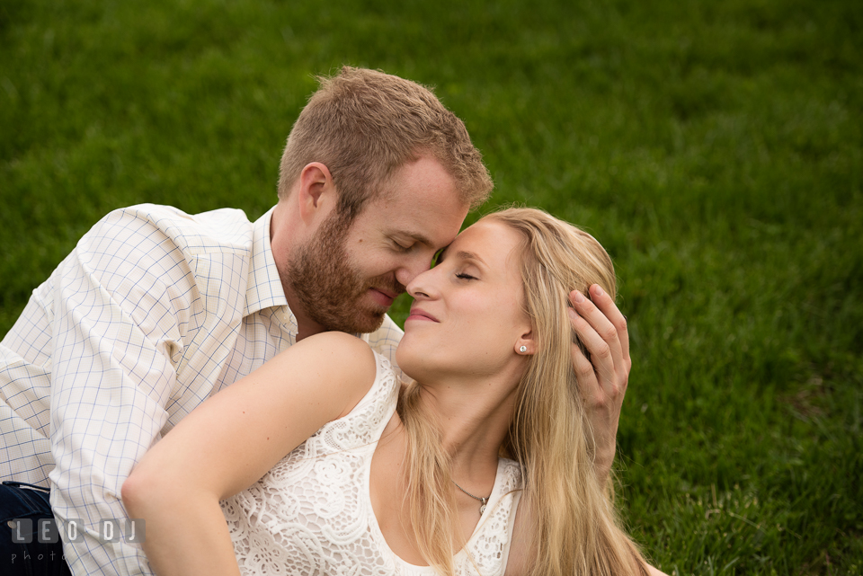 Engaged girl cuddling on the grass with her fiance. Quiet Waters Park Annapolis Maryland pre-wedding engagement photo session, by wedding photographers of Leo Dj Photography. http://leodjphoto.com