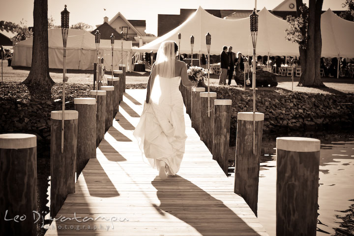 Bride holding bouquet and walking down the pier. Annapolis Kent Island Maryland Wedding Photography with live dance band at reception