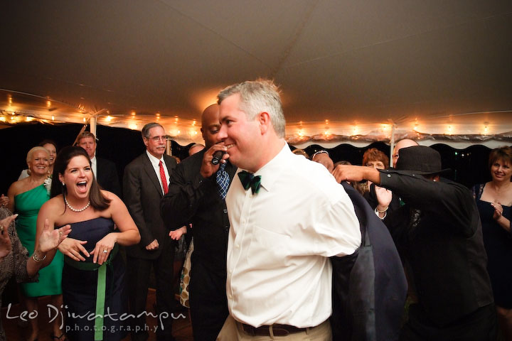 Groom takes off his jacket, helped by the wedding singers. Annapolis Kent Island Maryland Wedding Photography with live dance band at reception
