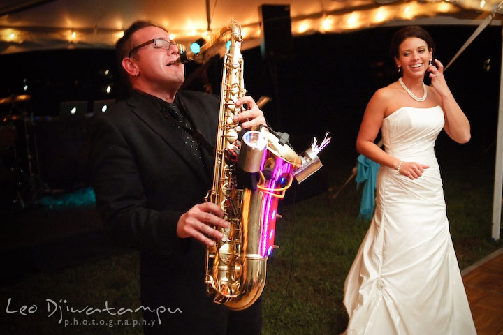 Saxohponist showing lights and sparkle display to bride. Annapolis Kent Island Maryland Wedding Photography with live dance band at reception