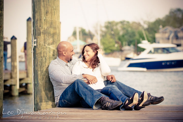 Engaged couple sitting on the pier Annapolis downtown harbor. Annapolis Maryland USNA Pre-Wedding Engagement Photo Session by wedding photographer Leo Dj Photography