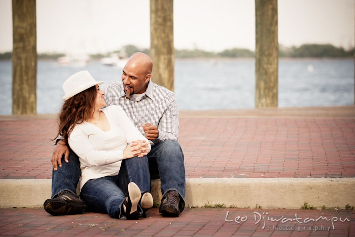 Guy smoking cigar, talking with his fiancée by the water. Annapolis Maryland USNA Pre-Wedding Engagement Photo Session by wedding photographer Leo Dj Photography