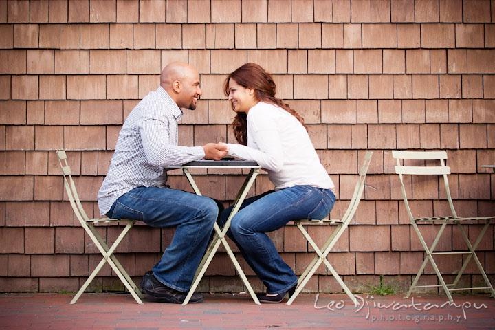 Engaged couple sitting at restaurant table outside. Annapolis Maryland USNA Pre-Wedding Engagement Photo Session by wedding photographer Leo Dj Photography