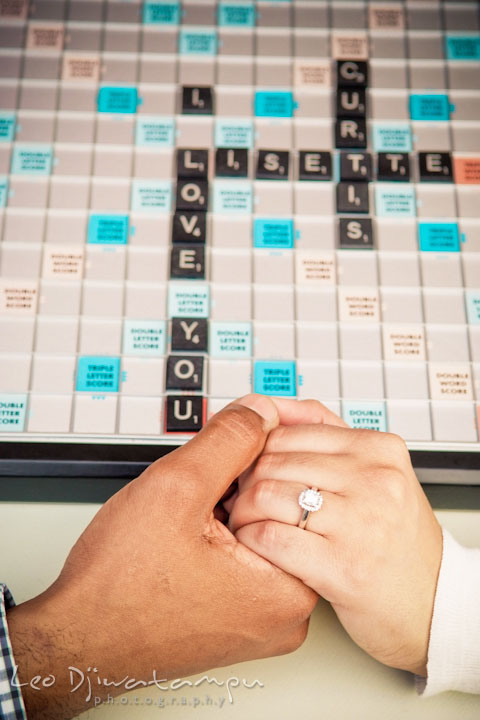I love you on scrabble board. Engaged couple holding hands, showing engagement ring. Annapolis Maryland USNA Pre-Wedding Engagement Photo Session by wedding photographer Leo Dj Photography