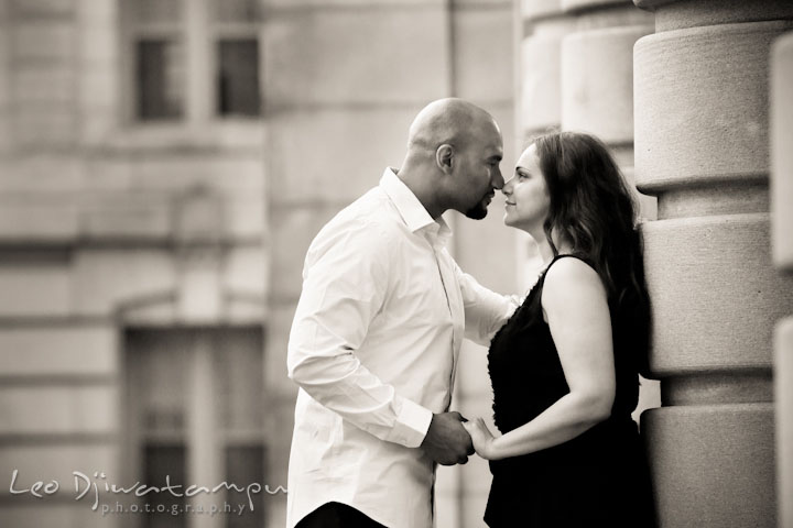 Engaged guy and girl almost kissed by the USNA building columns. Annapolis Maryland USNA Pre-Wedding Engagement Photo Session by wedding photographer Leo Dj Photography