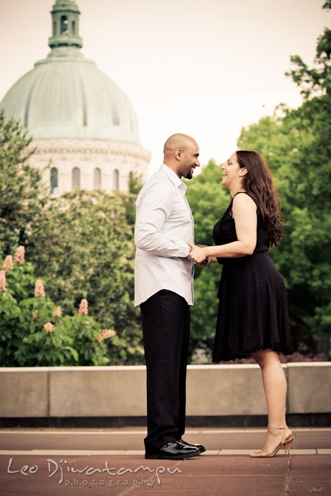 Engaged couple laughing with USNA chapel dome in the background. Annapolis Maryland USNA Pre-Wedding Engagement Photo Session by wedding photographer Leo Dj Photography