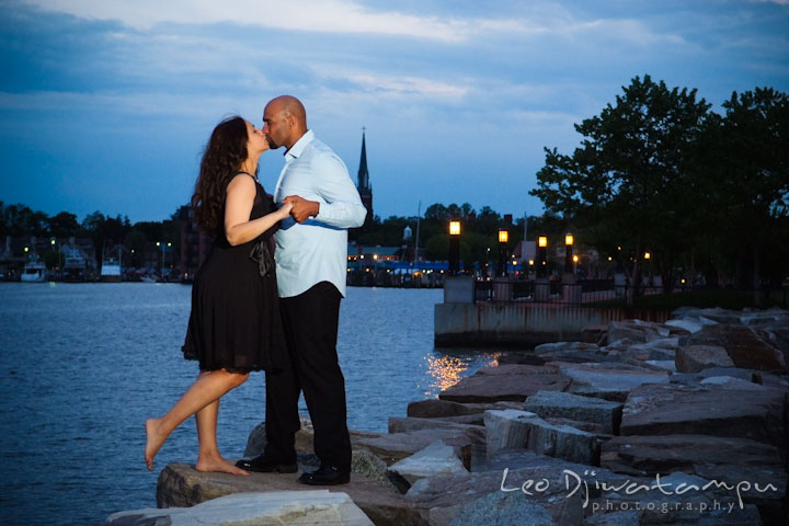 Engaged couple holding hand and kissing with Annapolis dowtown at night in the background. Annapolis Maryland USNA Pre-Wedding Engagement Photo Session by wedding photographer Leo Dj Photography