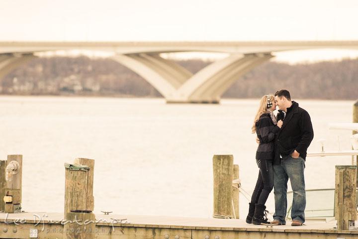 Engaged couple cuddling on boat dock with bridge behind them. Old Town Alexandria Virgina Pre-wedding Engagement Photo Session Photographer, Leo Dj Photography