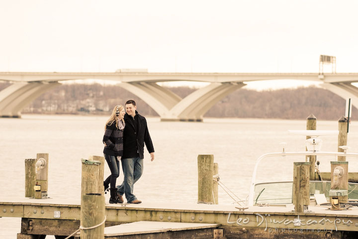 Fiancé and his fiancée walking on boat dock with bridge behind them. Old Town Alexandria Virgina Pre-wedding Engagement Photo Session Photographer, Leo Dj Photography