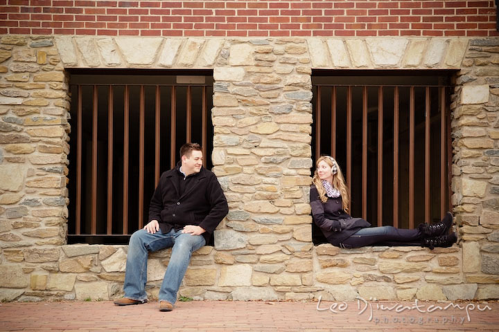 Engaged guy and girl sitting on brick wall window and looking at each other. Old Town Alexandria Virgina Pre-wedding Engagement Photo Session Photographer, Leo Dj Photography