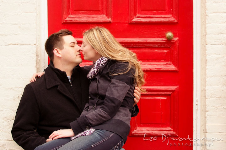 Engaged guy rubbing nose with his fiancée in front of a red door. Old Town Alexandria Virgina Pre-wedding Engagement Photo Session Photographer, Leo Dj Photography