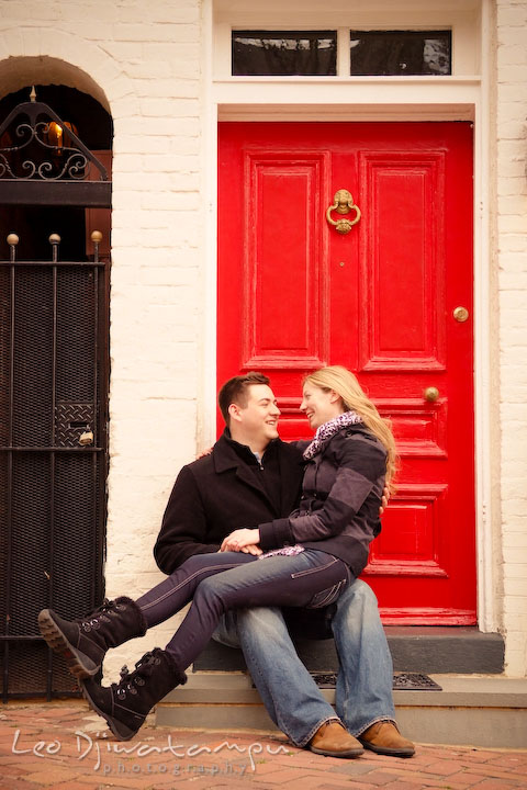 Engaged girl sitting on her fiancé's lap in front of a red door. Old Town Alexandria Virgina Pre-wedding Engagement Photo Session Photographer, Leo Dj Photography
