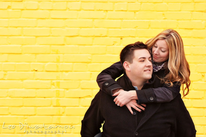 Engaged guy carrying his fiancée on his back with yellow brick wall behind them. Old Town Alexandria Virgina Pre-wedding Engagement Photo Session Photographer, Leo Dj Photography