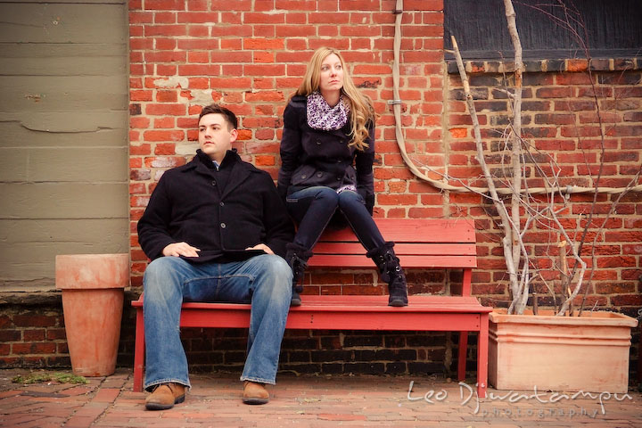 A fiancé and his fiancée sitting on a red bench and posing. Old Town Alexandria Virgina Pre-wedding Engagement Photo Session Photographer, Leo Dj Photography