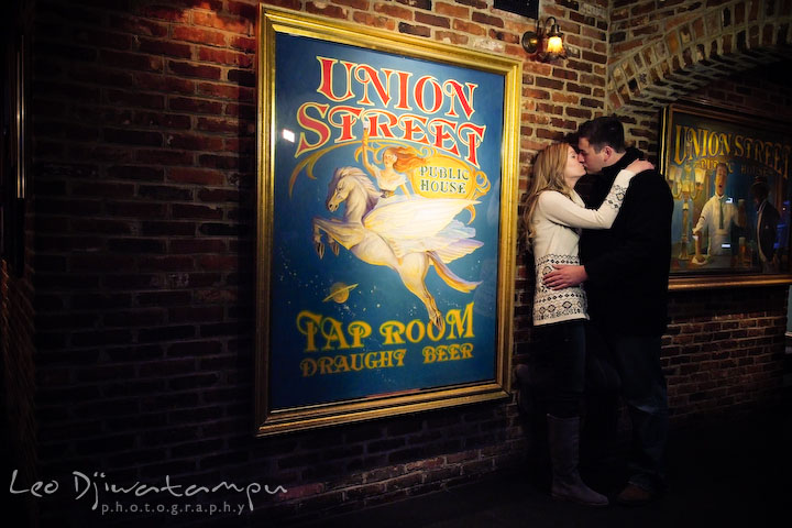 Engaged couple kissing by a cool painting inside a cool room. Old Town Alexandria Virgina Pre-wedding Engagement Photo Session Photographer, Leo Dj Photography