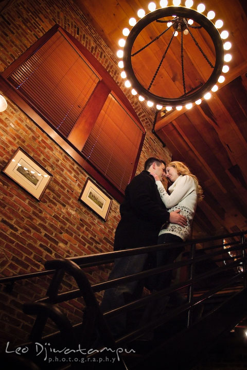 Engaged couple cuddling on the stairs, under a circular light. Old Town Alexandria Virgina Pre-wedding Engagement Photo Session Photographer, Leo Dj Photography