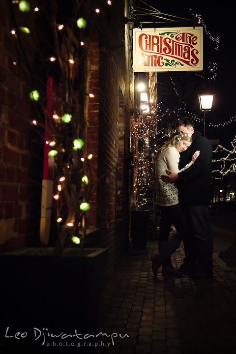 Enaged girl hugging her fiancé in front of a Christmas store, with lights around them. Old Town Alexandria Virgina Pre-wedding Engagement Photo Session Photographer, Leo Dj Photography