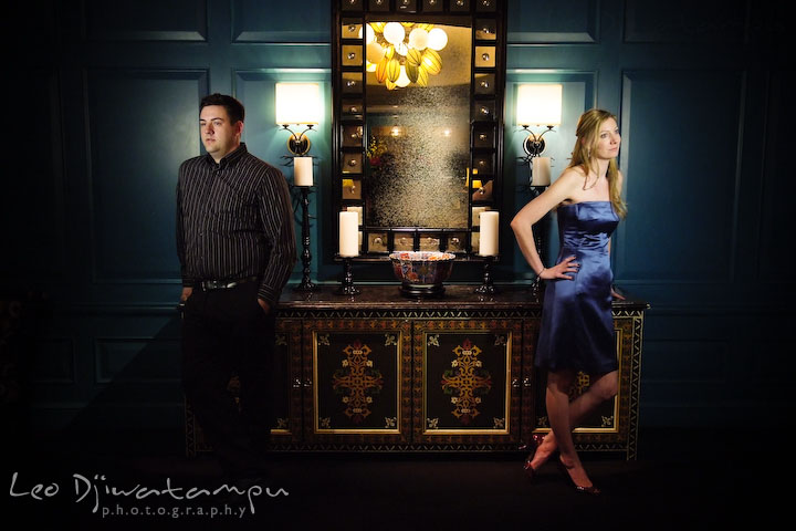 Engaged guy and girl standing opposite each other by an antique dressser and mirror. Old Town Alexandria Virgina Pre-wedding Engagement Photo Session Photographer, Leo Dj Photography