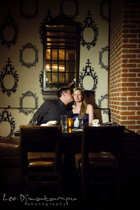 Engaged guy kissing girl's cheek in a restaurant with antique interior and decoration. Old Town Alexandria Virgina Pre-wedding Engagement Photo Session Photographer, Leo Dj Photography