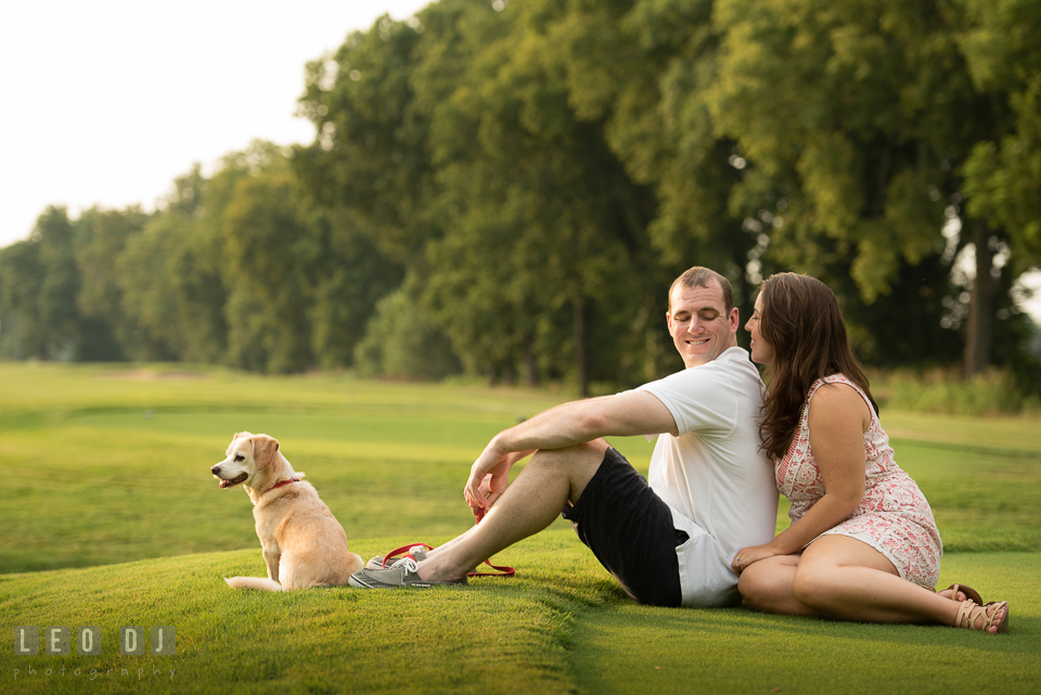 Engaged man lounging on the grass with his dog and fiancee. Leesburg Virginia pre-wedding engagement photo session at River Creek Club, by wedding photographers of Leo Dj Photography. http://leodjphoto.com
