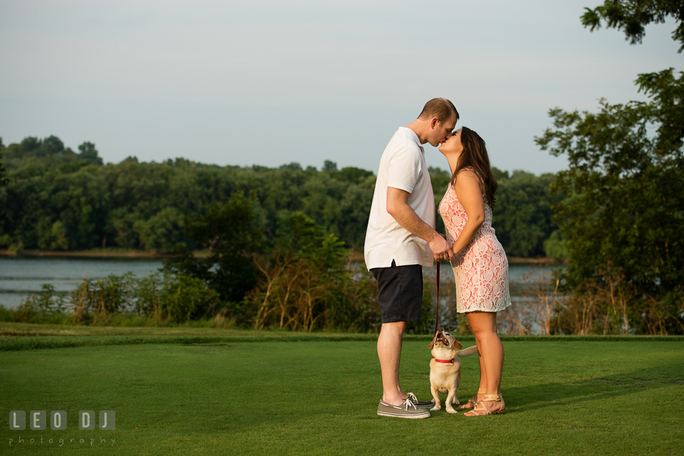 Engaged couple kissing while their dog looking at them. Leesburg Virginia pre-wedding engagement photo session at River Creek Club, by wedding photographers of Leo Dj Photography. http://leodjphoto.com
