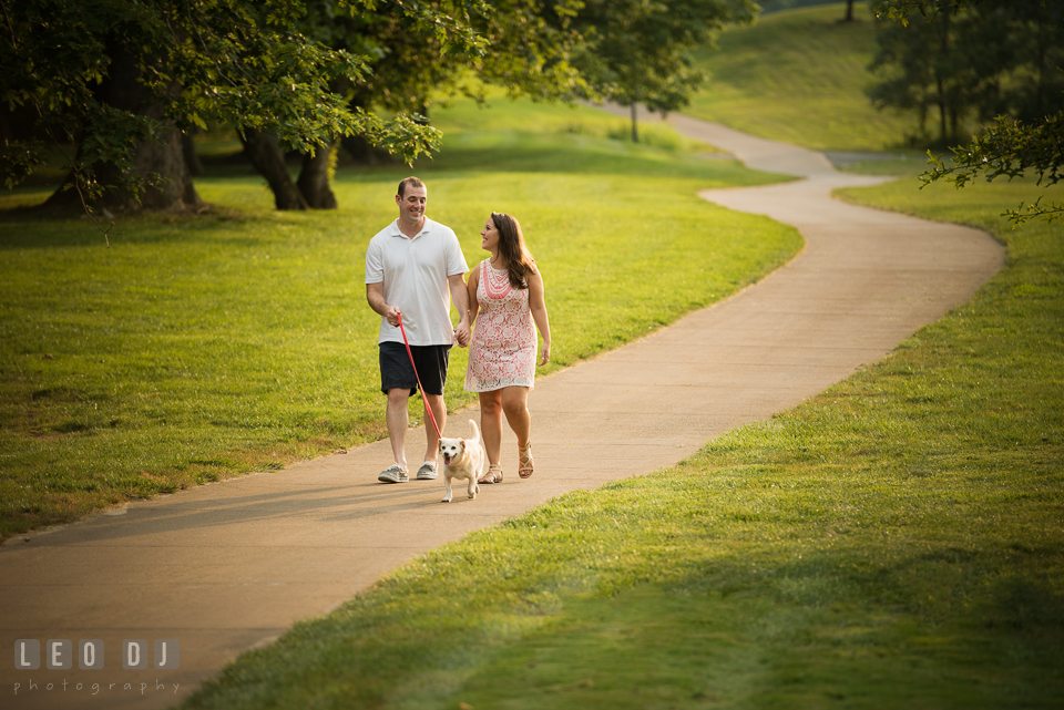 Engaged man and his fiance walking their dog down the path. Leesburg Virginia pre-wedding engagement photo session at River Creek Club, by wedding photographers of Leo Dj Photography. http://leodjphoto.com