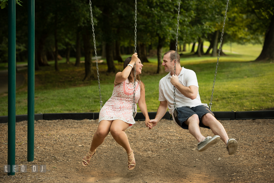 Engaged couple holding hands while playing on the swing. Leesburg Virginia pre-wedding engagement photo session at River Creek Club, by wedding photographers of Leo Dj Photography. http://leodjphoto.com