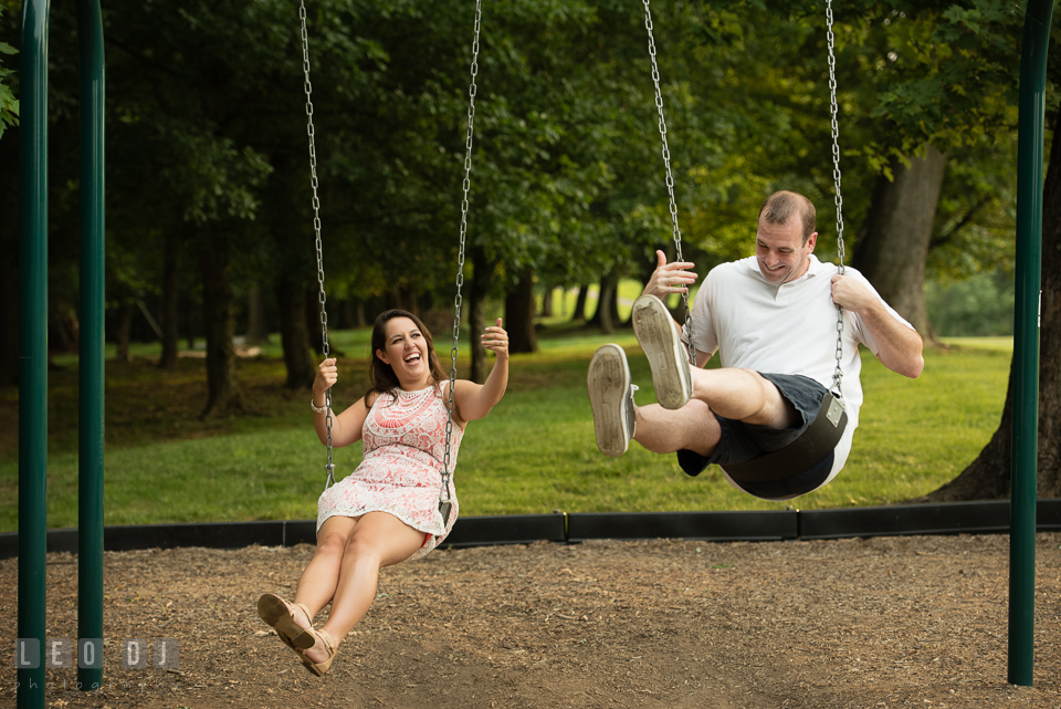 Engaged girl playing swing with her fiance, having fun and laughing. Leesburg Virginia pre-wedding engagement photo session at River Creek Club, by wedding photographers of Leo Dj Photography. http://leodjphoto.com