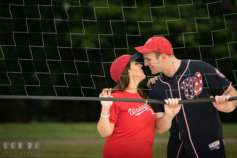 Engaged couple with MLB Washington Nationals jersey and cap almost kissing. Leesburg Virginia pre-wedding engagement photo session at River Creek Club, by wedding photographers of Leo Dj Photography. http://leodjphoto.com