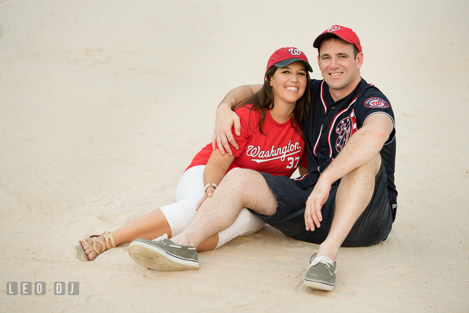 Engaged couple with MLB Washington Nationals jersey and cap lounging on the white sand. Leesburg Virginia pre-wedding engagement photo session at River Creek Club, by wedding photographers of Leo Dj Photography. http://leodjphoto.com