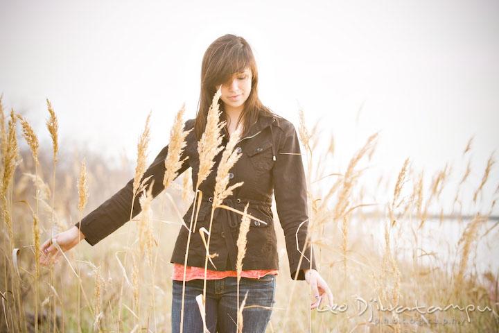 girl walking in meadow touching straws. Kent Island Annapolis High School Senior Portrait