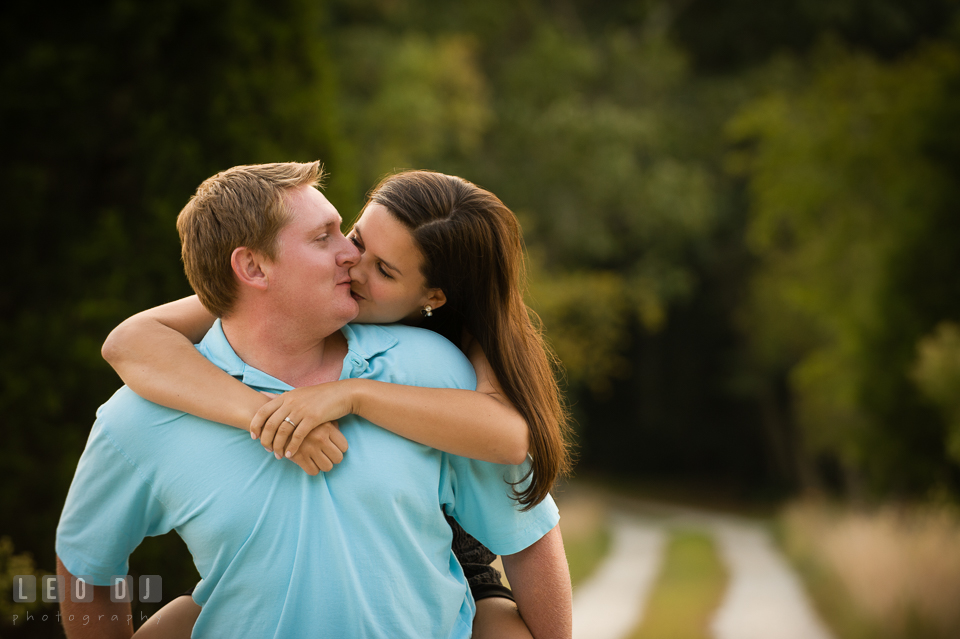 Engaged man carrying his fiancée on his back and kissing. Eastern Shore Maryland pre-wedding engagement photo session at Easton MD, by wedding photographers of Leo Dj Photography. http://leodjphoto.com