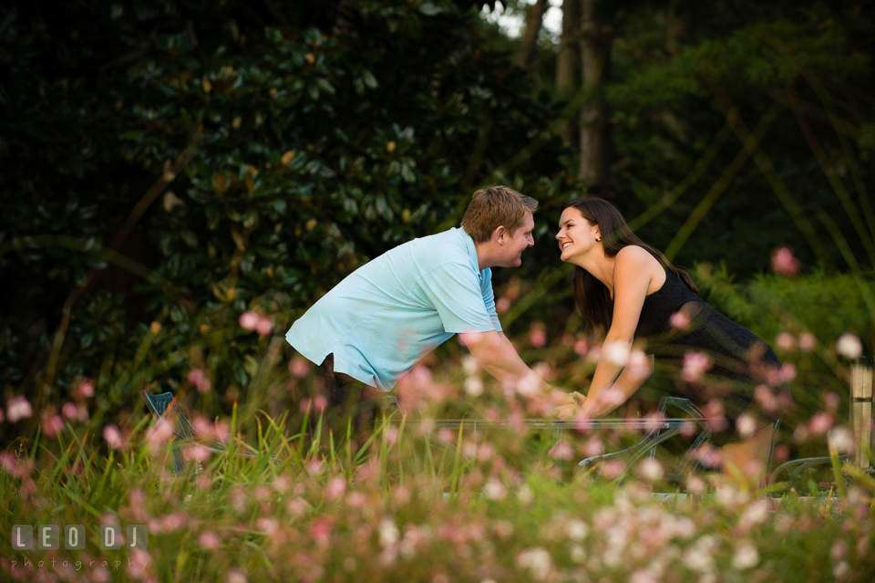 Engaged couple in a flower garden holding hands. Eastern Shore Maryland pre-wedding engagement photo session at Easton MD, by wedding photographers of Leo Dj Photography. http://leodjphoto.com