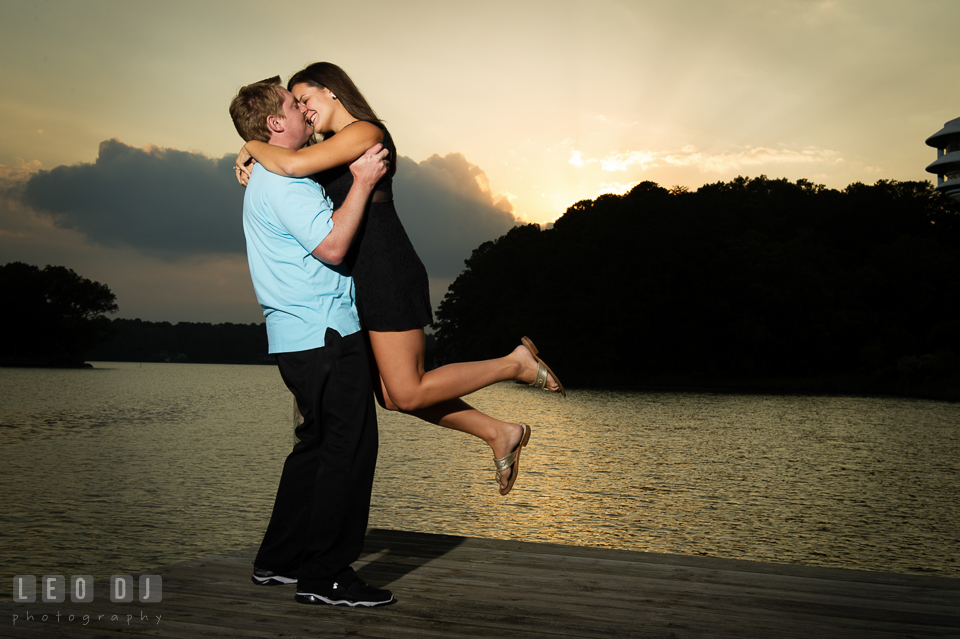 Engaged man lifted up his fiancee on the boat dock during sunset. Eastern Shore Maryland pre-wedding engagement photo session at Easton MD, by wedding photographers of Leo Dj Photography. http://leodjphoto.com