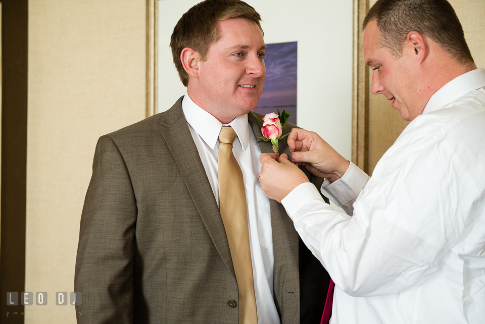 Best Man helps put on boutonniere on Groom. Hyatt Regency Chesapeake Bay wedding at Cambridge Maryland, by wedding photographers of Leo Dj Photography. http://leodjphoto.com