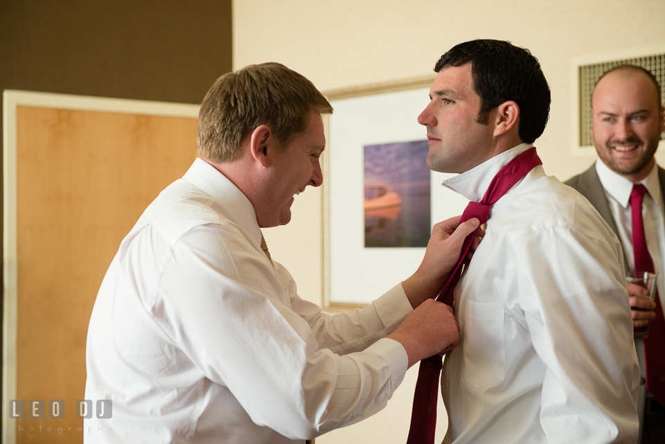 Groom helps Best Man with his tie. Hyatt Regency Chesapeake Bay wedding at Cambridge Maryland, by wedding photographers of Leo Dj Photography. http://leodjphoto.com
