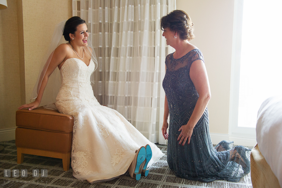 Bride and Mother of the Bride smiling after putting on Bride's shoes. Hyatt Regency Chesapeake Bay wedding at Cambridge Maryland, by wedding photographers of Leo Dj Photography. http://leodjphoto.com