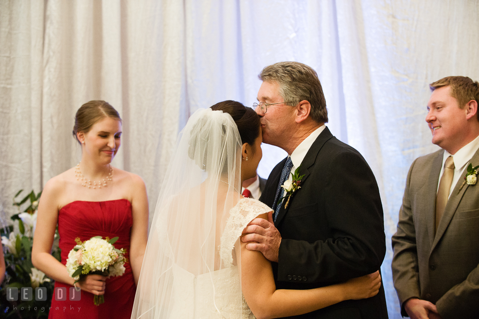 Father kissed Bride while giving away daughter during wedding ceremony. Hyatt Regency Chesapeake Bay wedding at Cambridge Maryland, by wedding photographers of Leo Dj Photography. http://leodjphoto.com