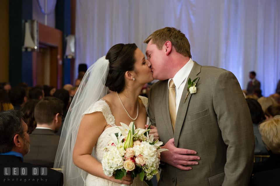 Bride and Groom kissing after recessional. Hyatt Regency Chesapeake Bay wedding at Cambridge Maryland, by wedding photographers of Leo Dj Photography. http://leodjphoto.com